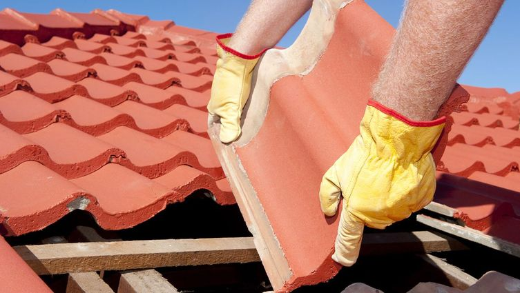 a roofer repairing a damaged roof tile
